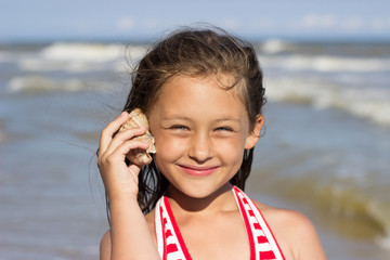 beautiful little girl put to the ear sea shell