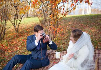 Groom shooting bride with retro camera in autumn park