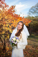 Young beautiful happy slim smiling bride in autumn forest