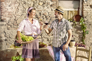 farming couple making a toast with a glass of wine, harvest time