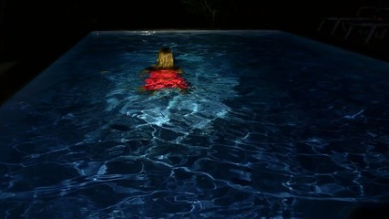 Young Female Swimming in Pool Water at Night. Slow Motion.
