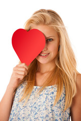 Beautiful young blonde woman with blue eyes holding red hart ban