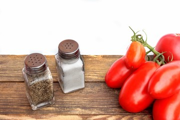 Fresh tomatoes and shakers on vintage wooden board