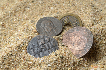 ancient coins in the sand