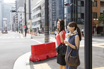 Two women to the signal waiting