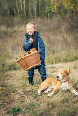 Happy Little boy with basket full of mushrooms with the dog on f