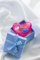 Blue present box with pink heart of glass in it