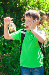 boy with a backpack and a clock in hands on nature