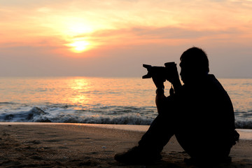 Silhouette photographer sitting on the beach