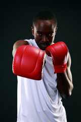 Portrait of an African American boxer punching in camera