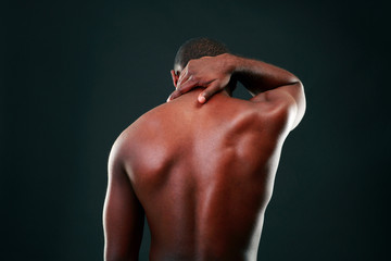 Back view portrait of african man over black background