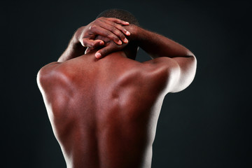 Back view portrait of a african man over black background