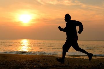 Silhouette man running at the beach
