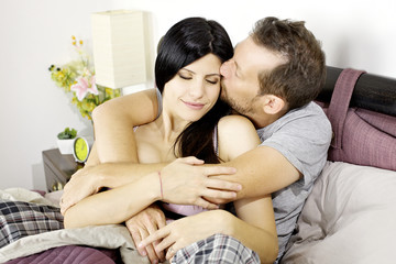 Man in love kissing wife in bed