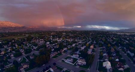 Aerial view of rainbow at sunset over neighborhood