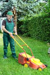 Gärtner mäht Wiese mit Rasenmäher
