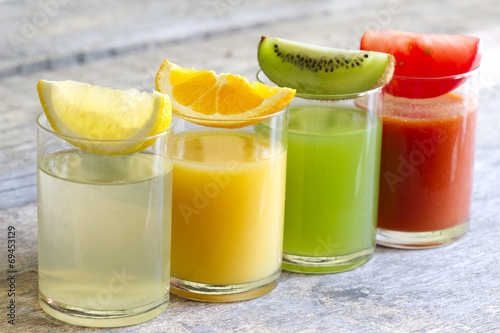 canvas print picture Fresh juice in glass with slices of fruits and vegetables