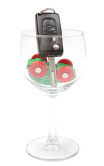Overturned model vehicle and car key in glass of wine.