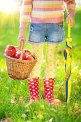 Child holding basket with apples