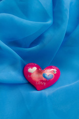 Glossy pink heart of glass on blue background