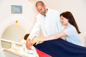 Medical technical assistant preparing scan of the spine with MRI