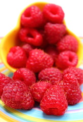Fresh raspberries pouring out of yellow bowl