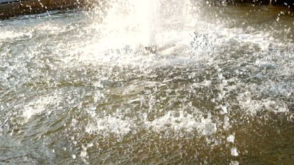 Wter falling down in fountain, ripples on water surface