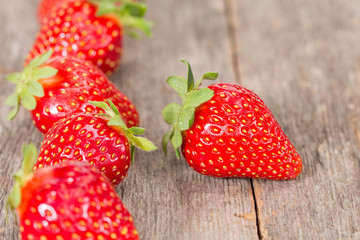 Strawberries in a row on wooden background
