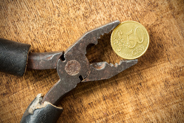 Euro cent and pliers on the wooden background