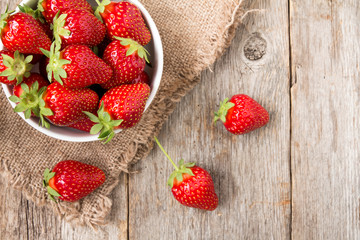 Bowl with strawberry on wooden background