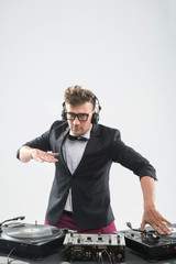 DJ in tuxedo having fun and dancing by the turntable