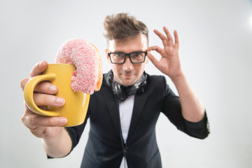 Dj handsome hipster eating donut from his cup on working place