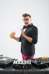 Dj eating donut on working place turntable