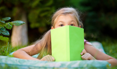 Little girl is hiding behind book outdoors