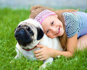 Little girl and her pug dog on green grass
