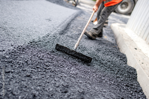 Worker leveling fresh asphalt on a road building
