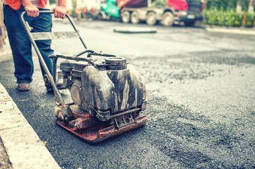 asphalt worker at road repairing and construction site