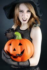 Hexe zu Halloween mit Kürbis