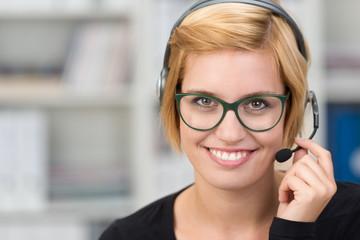 lächelnde frau mit headset im büro