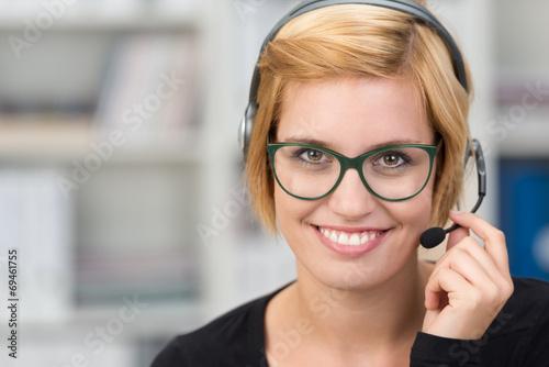 Leinwanddruck Bild lächelnde frau mit headset im büro