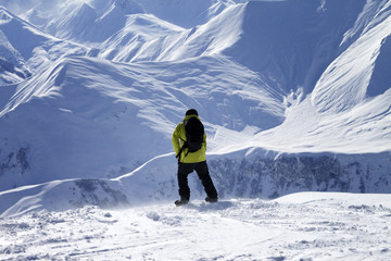 Snowboarder on top of off-piste slope at windy day