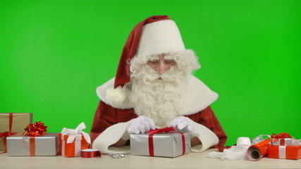 Santa Claus is Wrapping a Gift with Silver Colored Paper