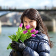 Happy beautiful girl with tulips enjoying spring day in Paris