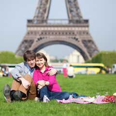 Happy young couple having a picnic near the Eiffel Tower