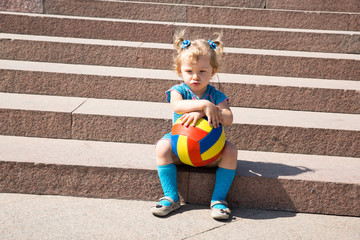 Adorable little child girl with toy ball on stairs .