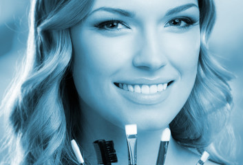 Smiling woman with make up tools