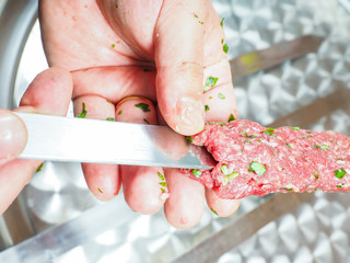 A chef making shish kebab of red meat with parsley over metal pl