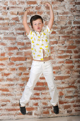 a little boy of 7 years, in a shirt with bananas, white trousers