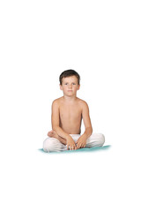 a little boy 7 years old, sitting in the Lotus posture, yoga