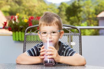Kleiner Junge nippt an Milchgetränk